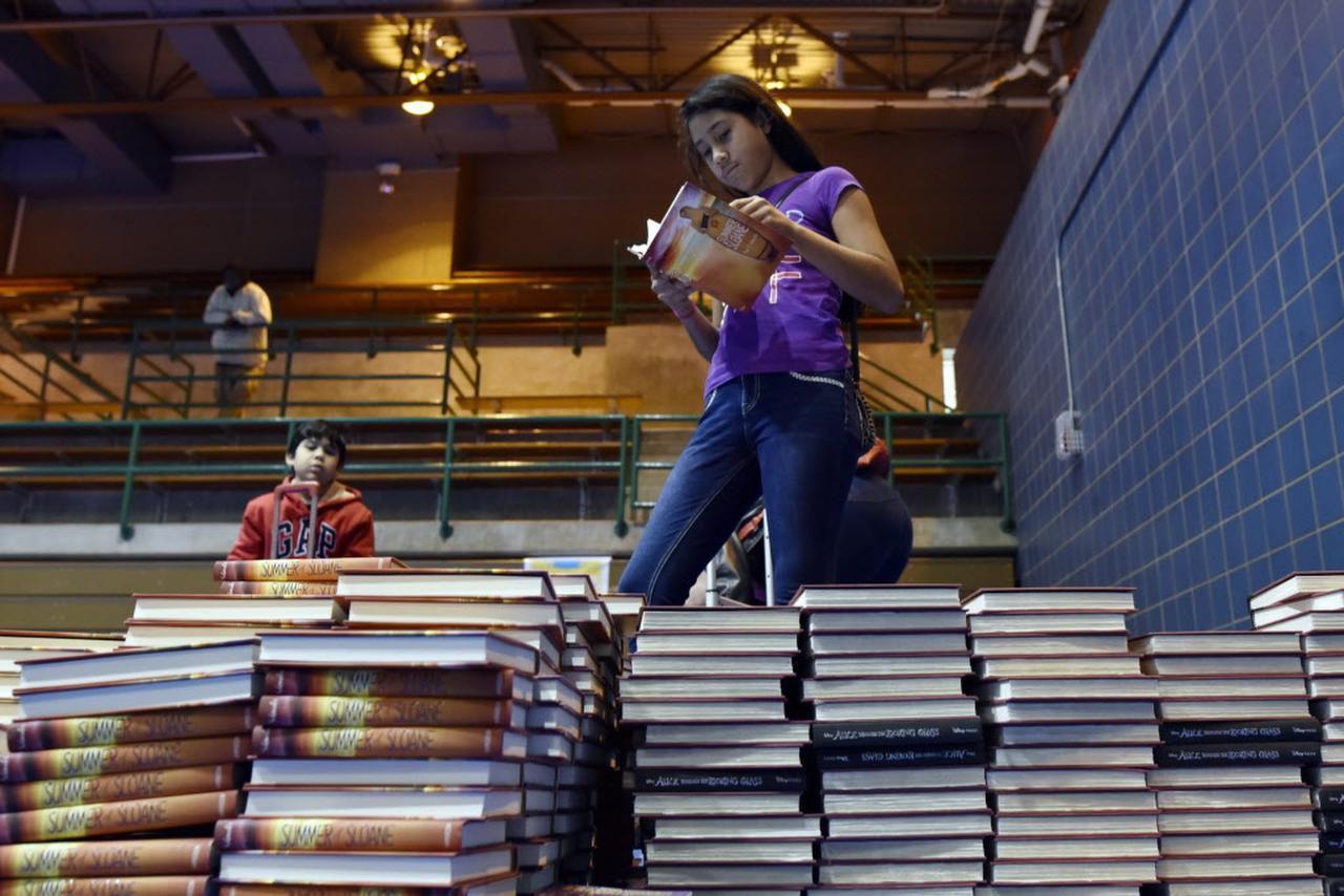 Evelyn Herrero revisa los libros disponibles en una feria de donación de libros que se realizó en el PC Cobb Athletic Complex, en Dallas. (ESPECIAL PARA AL DÍA/BEN TORRES)