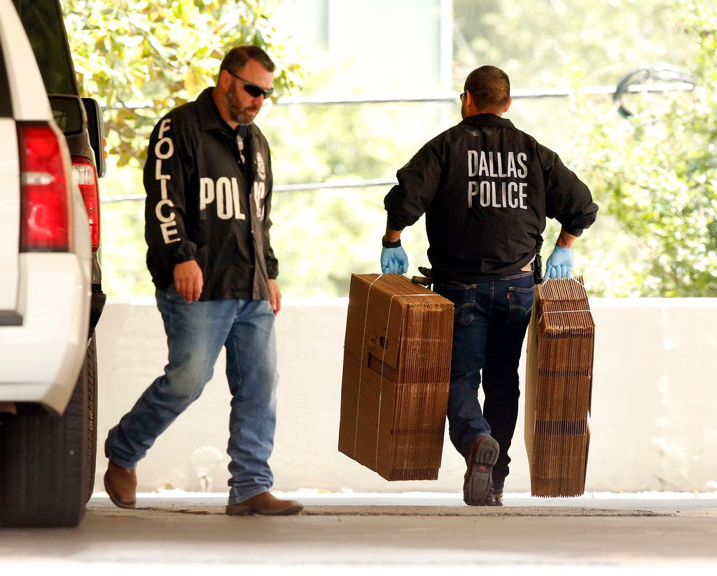 """Dallas police officials carry cardboard boxes Wednesday into the Catholic Diocese of Dallas as they continued to gather evidence. Dallas police on Wednesday morning raided several Dallas Catholic Diocese offices after a detective said church officials have """"thwarted"""" his investigations into allegations of sexual abuse by priests. Dallas Bishop Edward J. Burns said at an afternoon news conference that the diocese had given personnel files """"for all the priests named in the warrant"""" and had been has been cooperating with the police requests."""