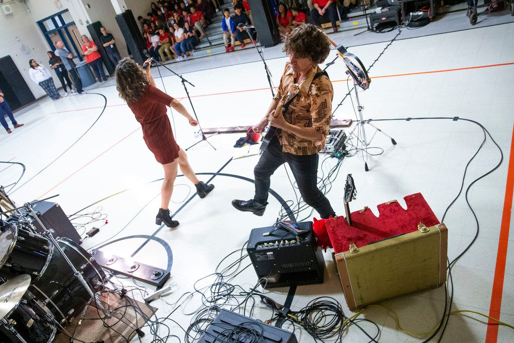 Erin O'Neill and Steve Gooding of the band Gooding perform at Bussey Middle School in Garland. The band alternated between playing music and talking about the basics of managing money.