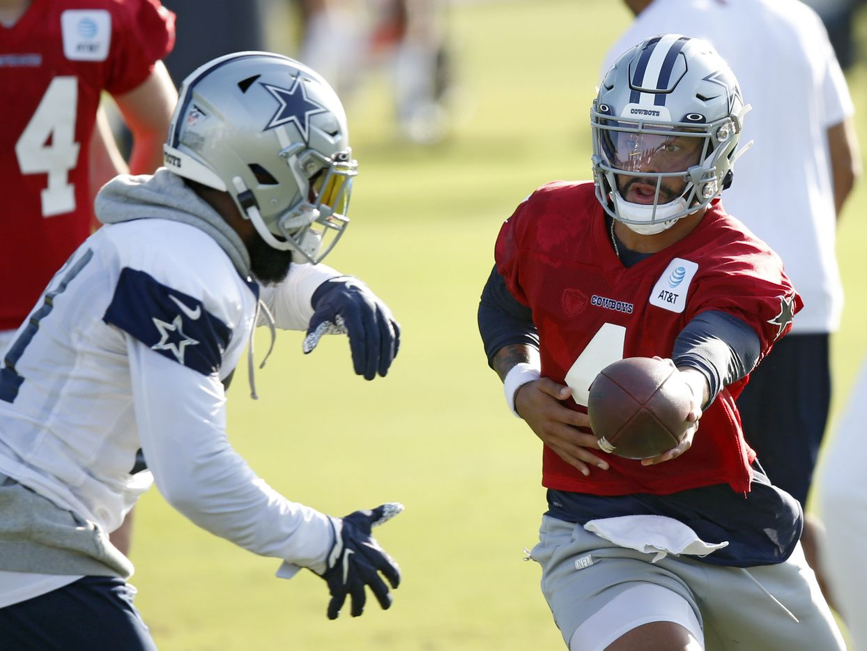 Dallas Cowboys quarterback Dak Prescott (4) hands the ball off to Dallas Cowboys running back Ezekiel Elliott (21) during the first day of training camp at Dallas Cowboys headquarters at The Star in Frisco, Texas on Friday, August 14, 2020. (Vernon Bryant/The Dallas Morning News)