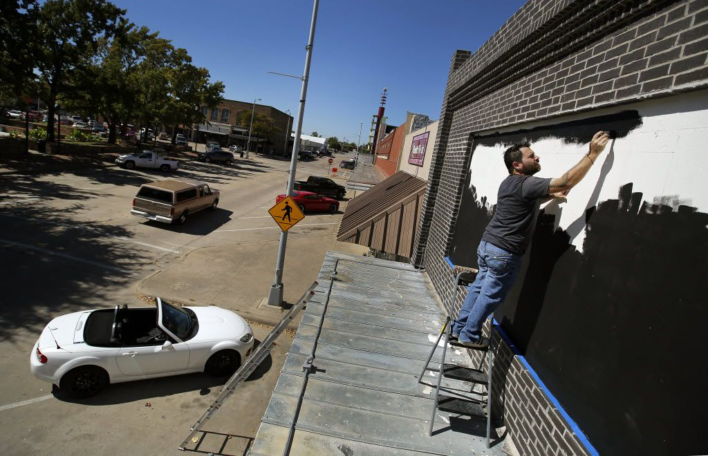 Painter and tattoo artist Lucas Cervellini paints the marquee on the new Intrinsic Smokehouse & Brewery storefront on the downtown Garland Square, Tuesday October 13, 2015.