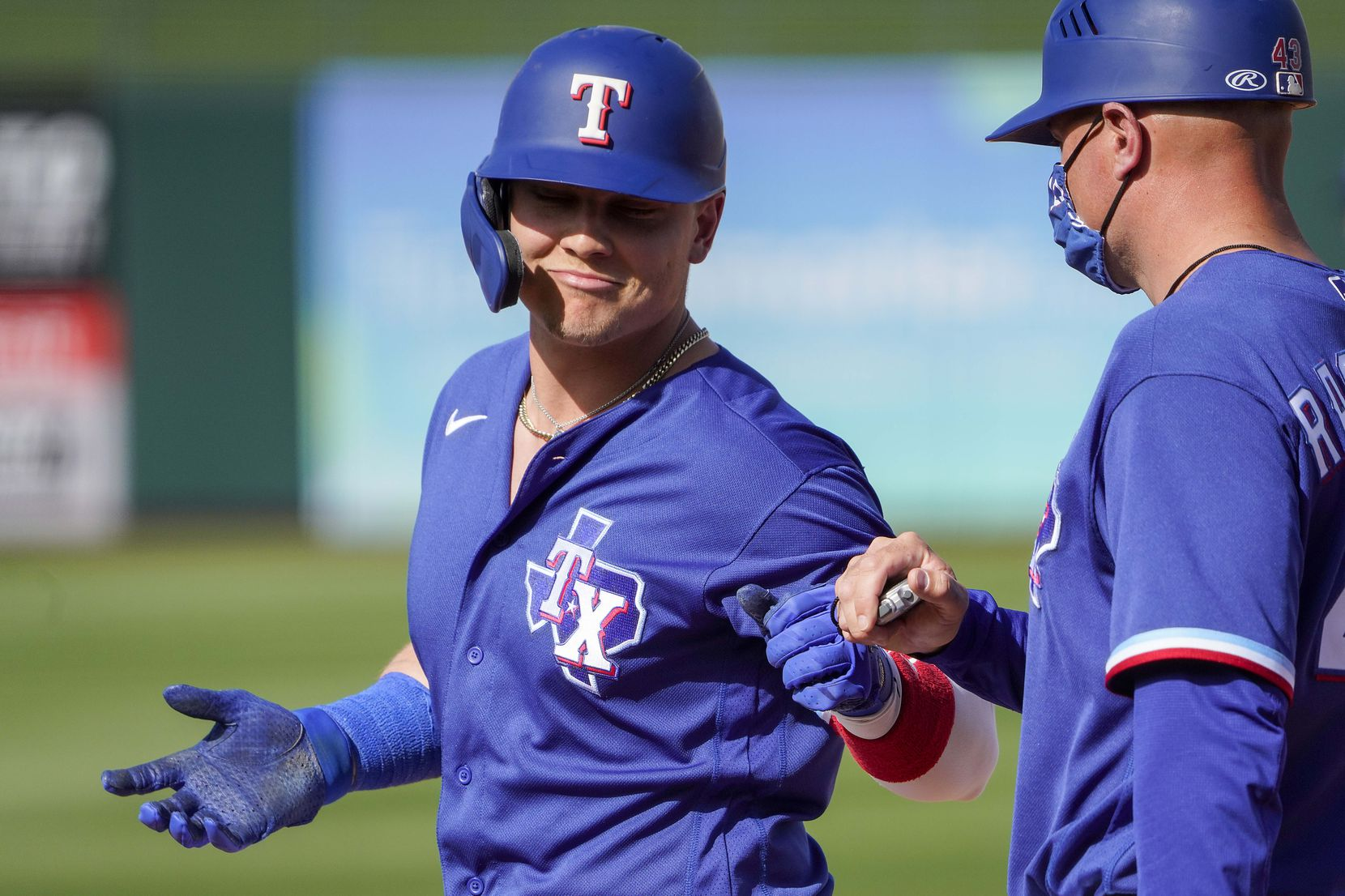 Texas Rangers outfielder Steele Walker celebrates with first base coach Corey Ragsdale after reaching on a single during the eighth inning of a spring training game against the Los Angeles Dodgers at Surprise Stadium on Sunday, March 7, 2021, in Surprise, Ariz.