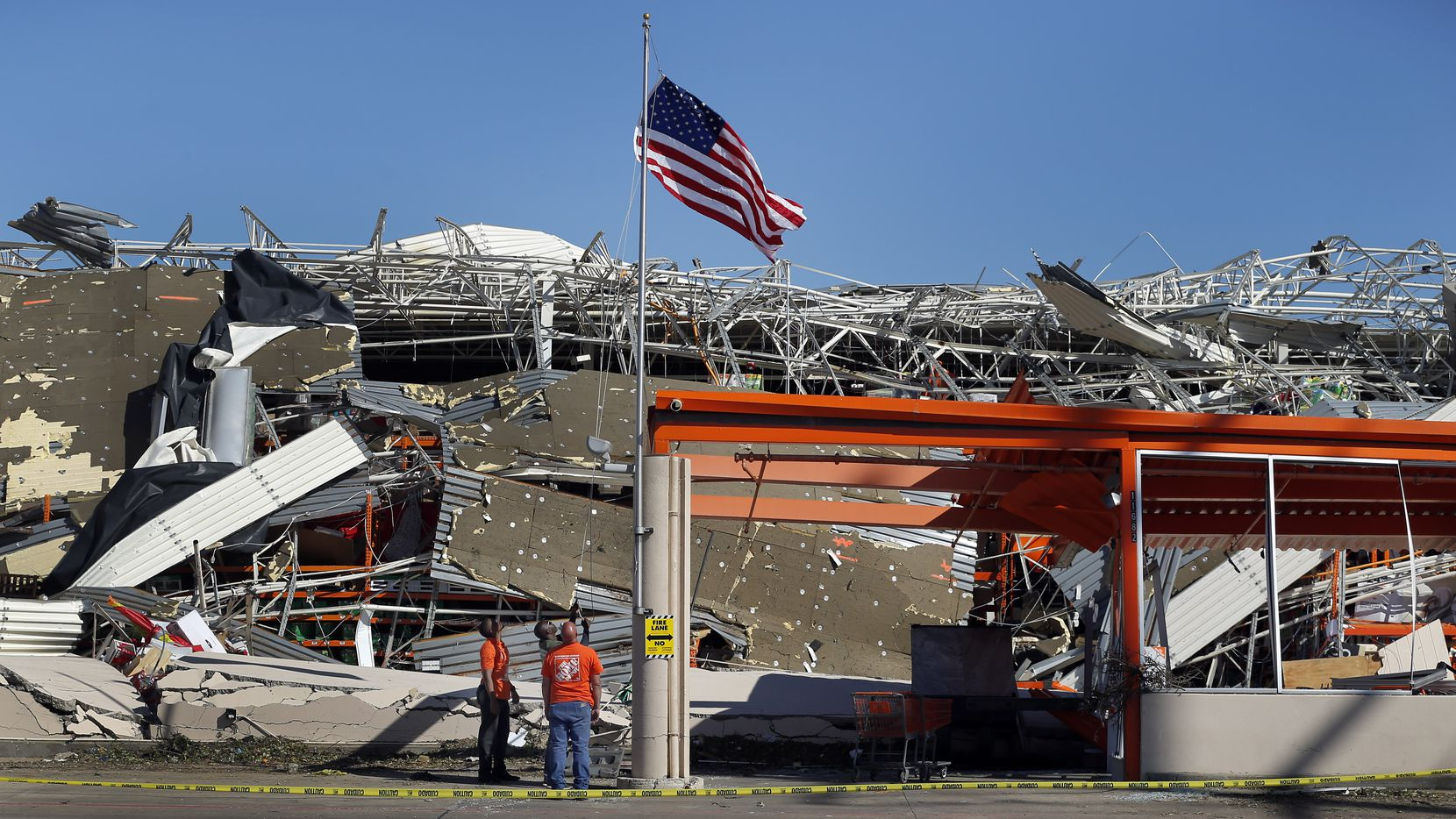 The Home Depot employees A.J. Kobena (center) raised the U.S. flag on the slightly bent flagpole outside the destroyed store just east N. Central Expressway on Forest Lane in Dallas, Monday, October 21, 2019. Joining him were store manager Jonathan Shields and assistant store manager Jordan Jasper.  A tornado tore through the entire neighborhood knocking down trees and ripping roofs from homes.