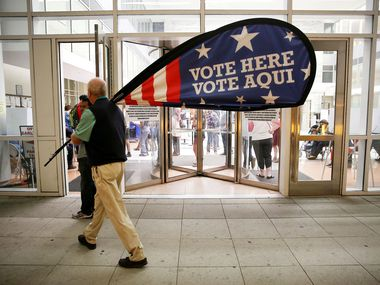 Election official Jimmy Murphy carries in a polling place sign while shutting down at the end of the night following the conclusion of early voting at the George L. Allen, Sr. Courts Building in downtown Dallas Nov. 4, 2016.