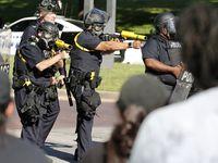Agentes de la Policía de Dallas posicionados para disparar contenedores de gas lacrimógeno durante una manifestación en el centro de Dallas, el sábado 30 de mayo.