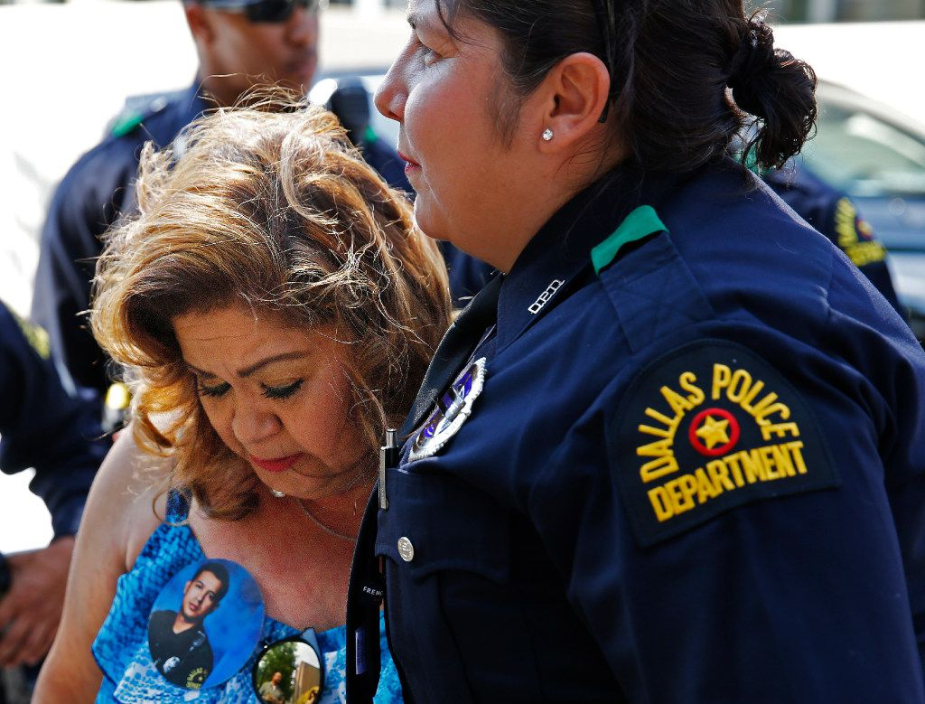 Members of the Dallas Police Department comforted Valerie Zamarripa, mother of Patrick Zamarripa, during the blessing of the fleets at the Cathedral Shrine of the Virgin of Guadalupe in June.