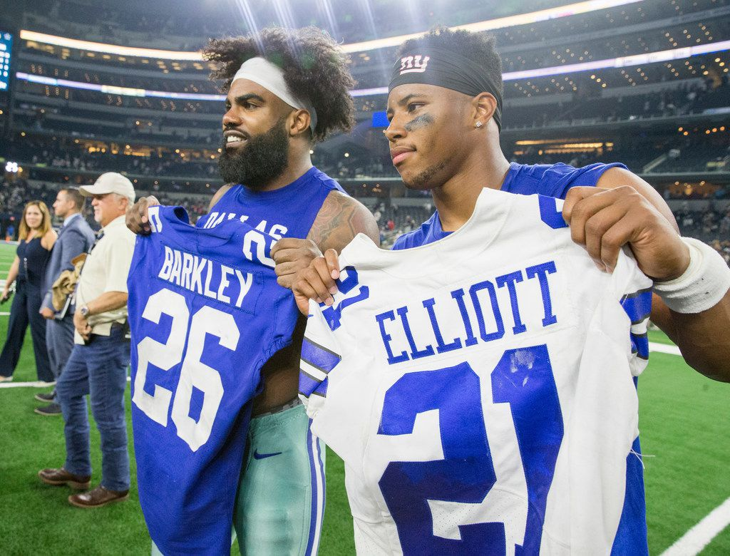 Dallas Cowboys running back Ezekiel Elliott (21) poses for pictures after exchanging jerseys with New York Giants running back Saquon Barkley (26) following an NFL game between the Dallas Cowboys and New York Giants on Sunday, September 16, 2018 at AT&T Stadium in Arlington, Texas. (Shaban Athuman/ The Dallas Morning News)