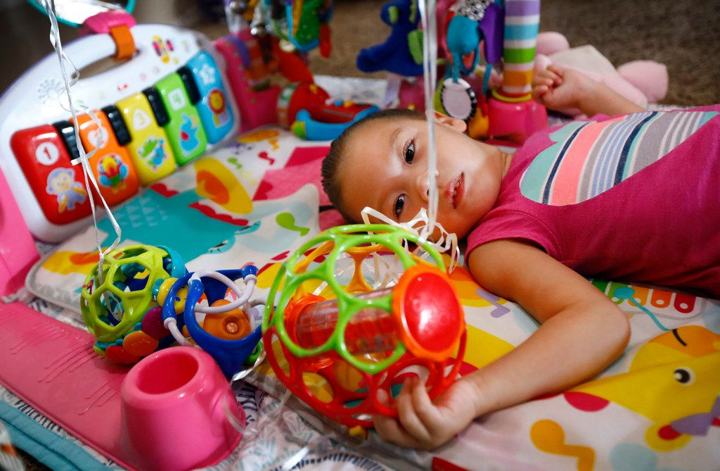 Annalynne Magallon, who has cerebral palsy, spends a lot of time on her back playing with her toys at her Burleson home on Friday, July 13. Jayme Magallon and her husband Brandon are one of many families who say they've considered divorce so that their sick or disabled children can be cared for through the unemployed parent's Medicaid. The situation is informally advised to many Texas families.