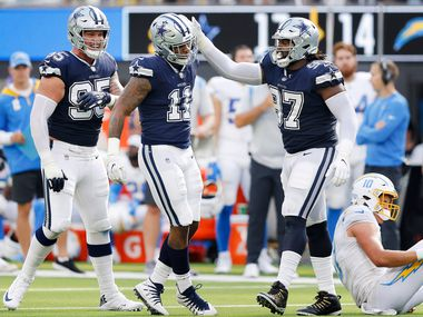 Dallas Cowboys linebacker Micah Parsons (11) is congratulated by defensive tackle Osa Odighizuwa (97) after his sack of Los Angeles Chargers quarterback Justin Herbert (right) during the fourth quarter at SoFi Stadium in Inglewood, California, Sunday, September 19, 2021. The Cowboys won, 20-17.