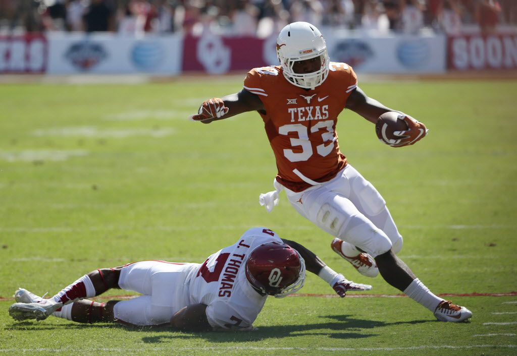 Texas Longhorns running back D'Onta Foreman (33) avoids a tackle by Oklahoma Sooners cornerback Jordan Thomas (7) in the first half during an NCAA football game between Oklahoma and Texas at the Cotton Bowl in Dallas Saturday October 10, 2015. Texas Longhorns beat Oklahoma Sooners 24-17. (Andy Jacobsohn/The Dallas Morning News)