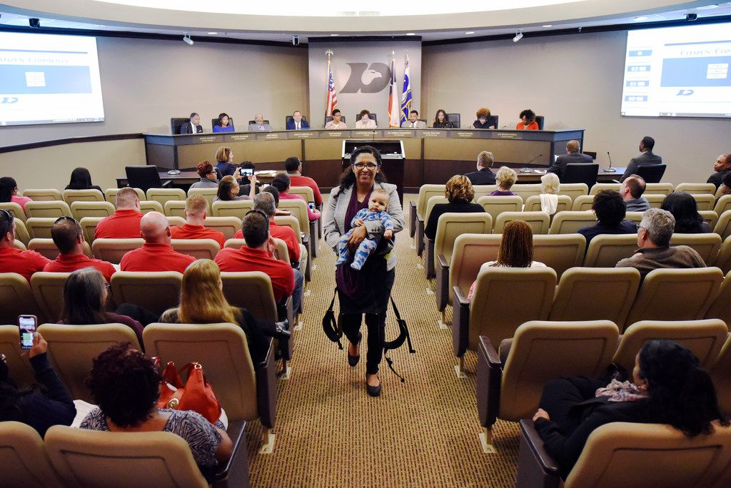 Candace Valenzuela, 34, of Dallas, with her baby, Jacinto Baldwin, walks back to her seat after discussing why she's in favor of a paid parental leave program for city employees in DeSoto.