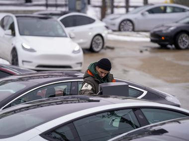 A line of cars waits for a charging station at the Tesla Supercharger on North Central Expressway near Walnut Hill on Tuesday, Feb. 16, 2021, in Dallas. More than 4 million Texans, many of them in North Texas, are fighting extended power outages. Another winter storm could dump 5 more inches of snow on Dallas-Fort Worth. (Smiley N. Pool/The Dallas Morning News)