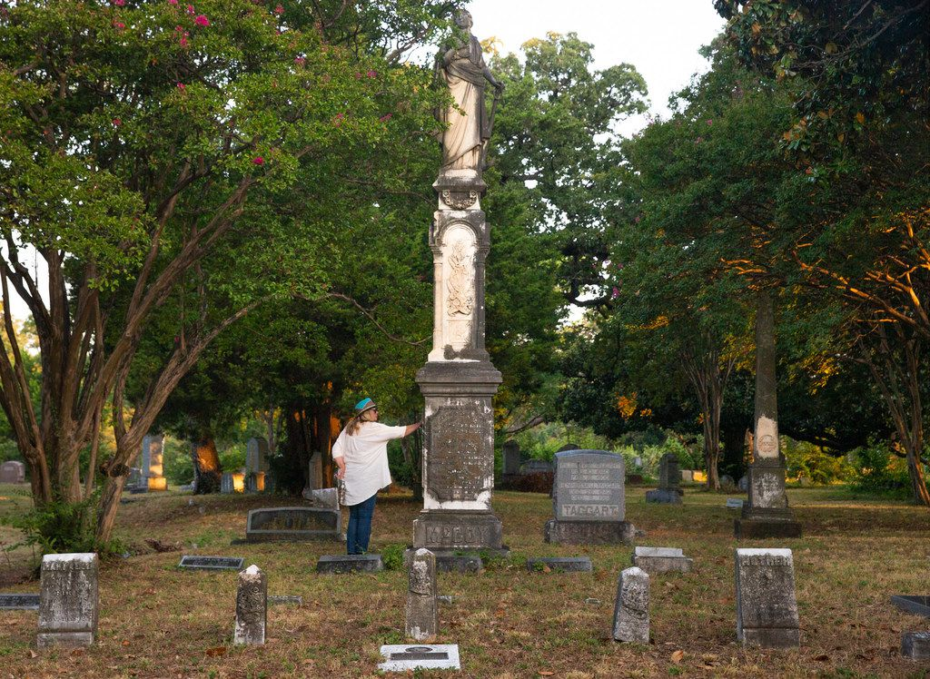 Brenna Elliott, founder of the Dallas History Guild, touches an obelisk headstone at the Oakland Cemetery. She has been sounding the alarm about the cemetery's unsure future.