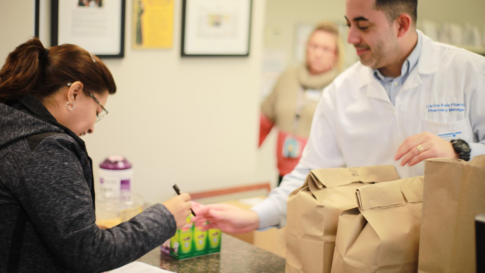 Carlos Irula, the pharmacist-in-charge at St. Vincent de Paul Pharmacy, helps a customer. The nonprofit has provided nearly $4 million in free prescriptions to North Texans in need during COVID-19.