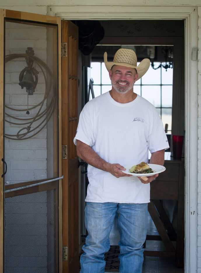 Mike Newton, known as the Cowboy Chef, holds his freshly prepared Pan Seared Sea Bass arocet with compound butter, served atop sauteed Bok Choy and Shitake Mushrooms with Mirin glaze on the back porch of his ranch house in Lipan, Texas on July 17, 2018. (Robert W. Hart/Special Contributor)