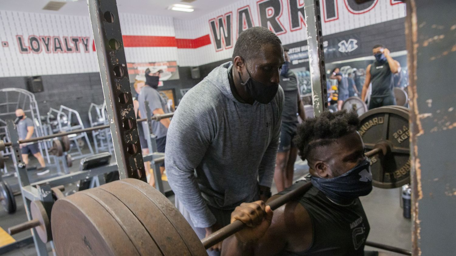 """Homicide Sergeant Brian Jones (left) from the Arlington Police Department spots for Arlington Martin Defensive tackle Marquis Evans during their workout at the school's gym as part of the """"Coach 5-0"""" program on Monday, Sept. 21, 2020 in Arlington."""