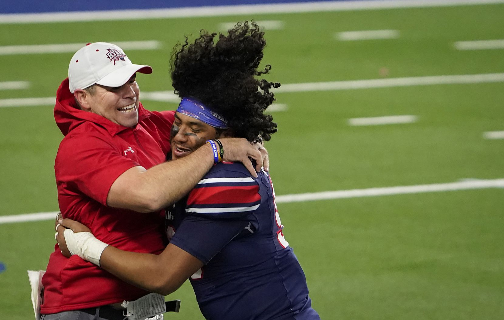 Denton Ryan offensive lineman Bryan Aguilar (56) hugs assistant coach Shane Tolleson as they celebrate a 59-14 victory over Cedar Park to win the Class 5A Division I state football championship game at AT&T Stadium on Friday, Jan. 15, 2021, in Arlington, Texas. (Smiley N. Pool/The Dallas Morning News)