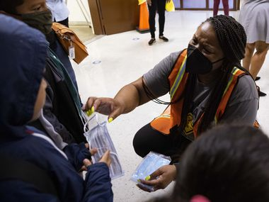 Principal Shanieka Christmas-McDonald hands out masks during the first day of school on Monday, Aug. 2, 2021, at H.I. Holland Elementary School in Dallas. (Juan Figueroa/The Dallas Morning News)