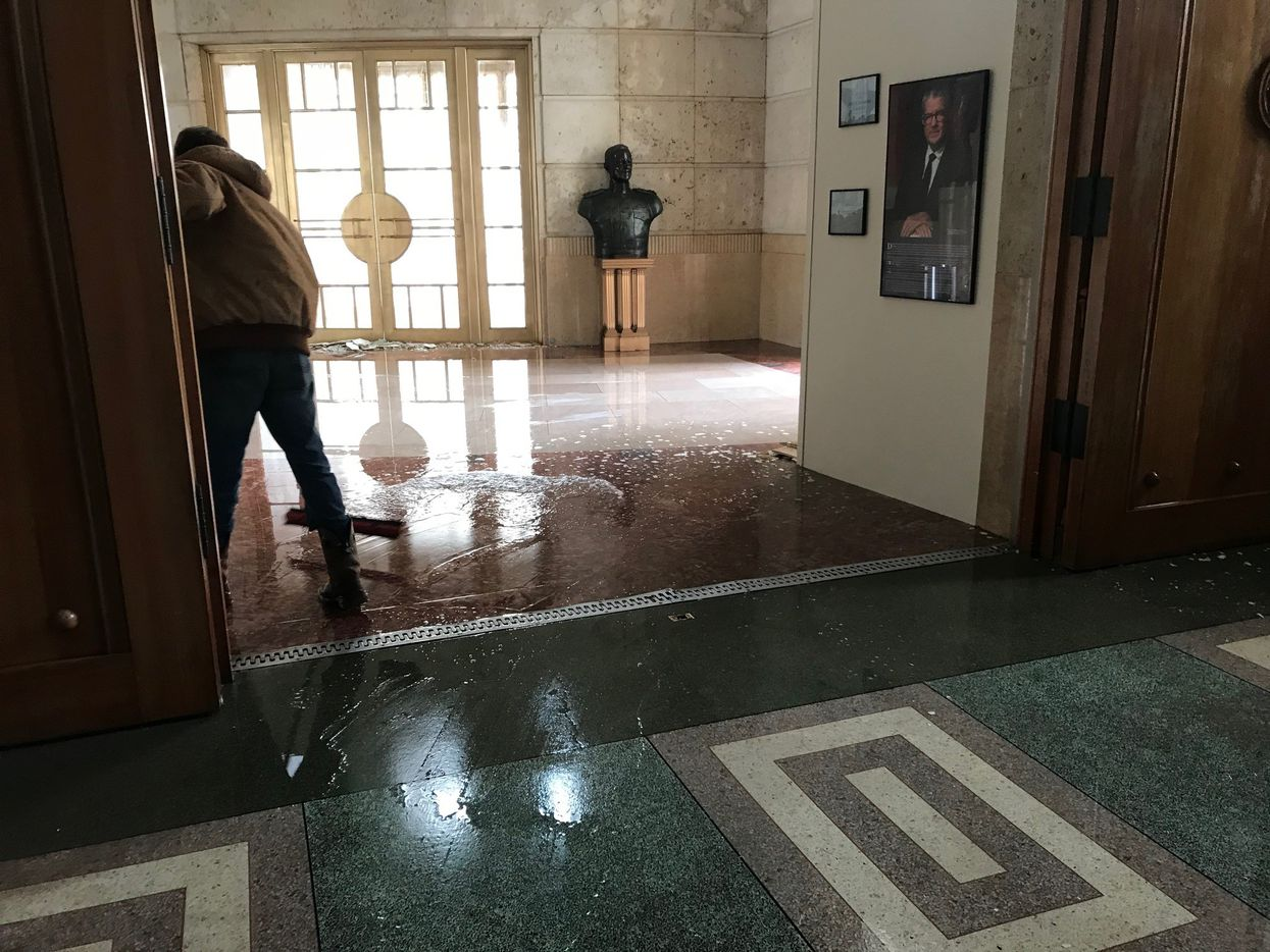 A photo shows water being swept out of the Hall of State in Dallas on Feb. 17, 2021. The building was one of several Fair Park facilities that sustained water damage from broken water pipes during the winter storm.