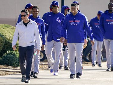 Texas Rangers general manager Jon Daniels (left) walks with players to a team meeting before the first spring training workout for pitchers and catchers at the team's training facility on Wednesday, Feb. 12, 2020, in Surprise, Ariz.