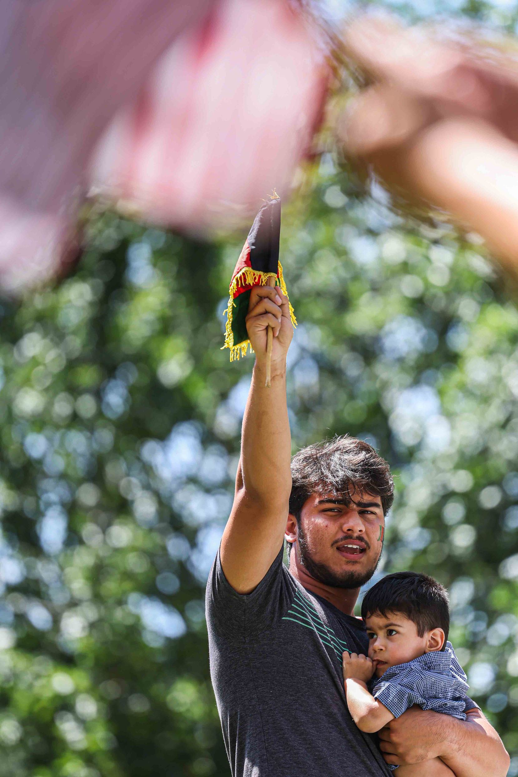Mohammad Mahbobyar, 19, who said he is a refugee from Afghanistan, was at the rally with his 1-year-old nephew, Suvan Yasiney.
