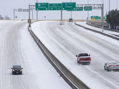 Snow covers Woodall Rodgers Freeway in Downtown Dallas on Monday. The snow has closed many city services and caused power outages in Frisco.