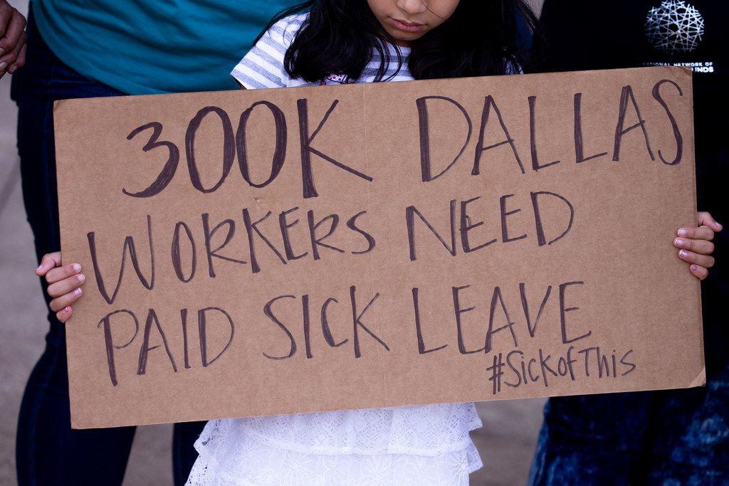 A  girl holds a sign during during a press conference about a paid sick time ordinance outside Dallas City Hall on June 20, 2019. The ordinance takes effect on Aug. 1, 2019.