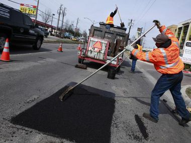 Gary Langley (right) and other Dallas city workers repair potholes on Lemmon Avenue in 2010.