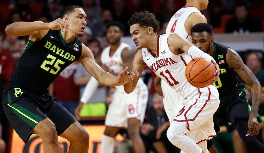 Oklahoma guard Trae Young (11) drives between Baylor forward Tristan Clark (25) and guard Tyson Jolly, right, during the first half of an NCAA college basketball game in Norman, Okla., Tuesday, Jan. 30, 2018.