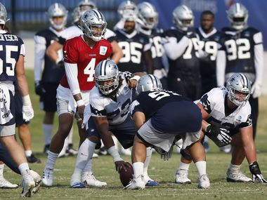 Dallas Cowboys center Joe Looney (73) makes a point as Dallas Cowboys quarterback Dak Prescott (4) prepares to run the play during training camp at the Dallas Cowboys headquarters at The Star in Frisco, Texas on Sunday, August 16, 2020.