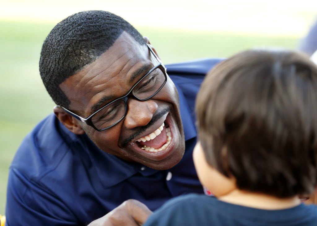 Former Dallas Cowboys Hall of Fame receiver Michael Irvin (left) took a liking to Dallas Cowboys fan Giovanni Arzola, 1, of Camarillo, California as he was signing autographs for fans following afternoon practice at training camp in Oxnard, California, Wednesday, August 10, 2016. (Tom Fox/The Dallas Morning News)