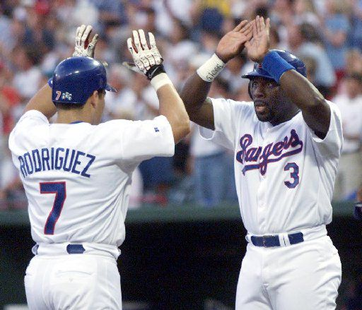 ORG XMIT: S11AA4207 8/1/99--Texas Rangers Ivan Rodriguez celebrates his two-run home-run with Mark Mclemore at home plate in the third inning against the Kansas City Royals.  Rodriguez's home-run started the Rangers eight run drive in the third. (
