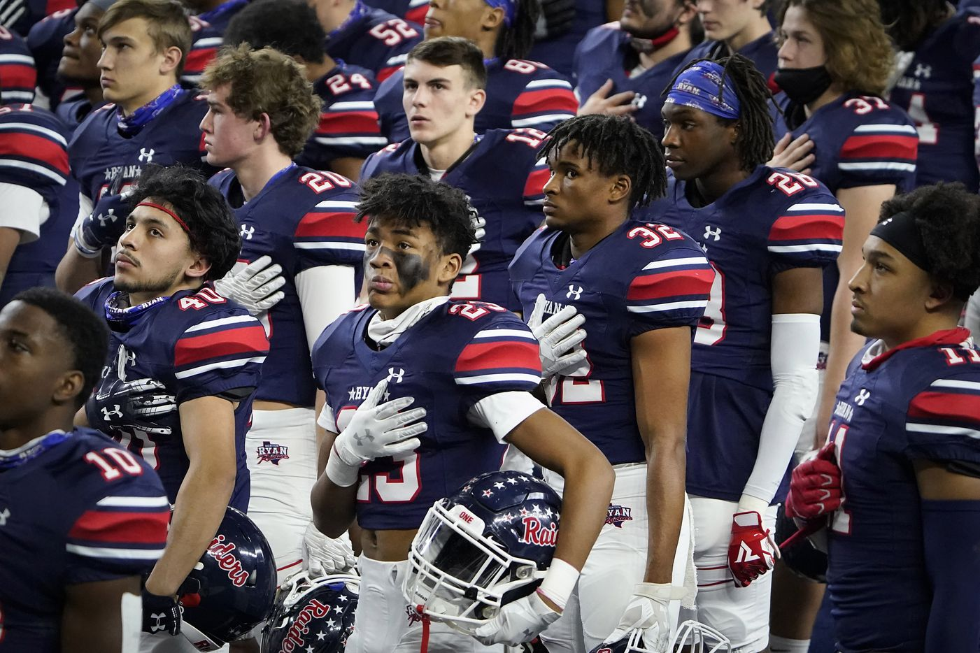 Denton Ryan players, including defensive back James Lundy (23), stand for the national anthem before facing Cedar Park in the Class 5A Division I state football championship game at AT&T Stadium on Friday, Jan. 15, 2021, in Arlington, Texas. (Smiley N. Pool/The Dallas Morning News)