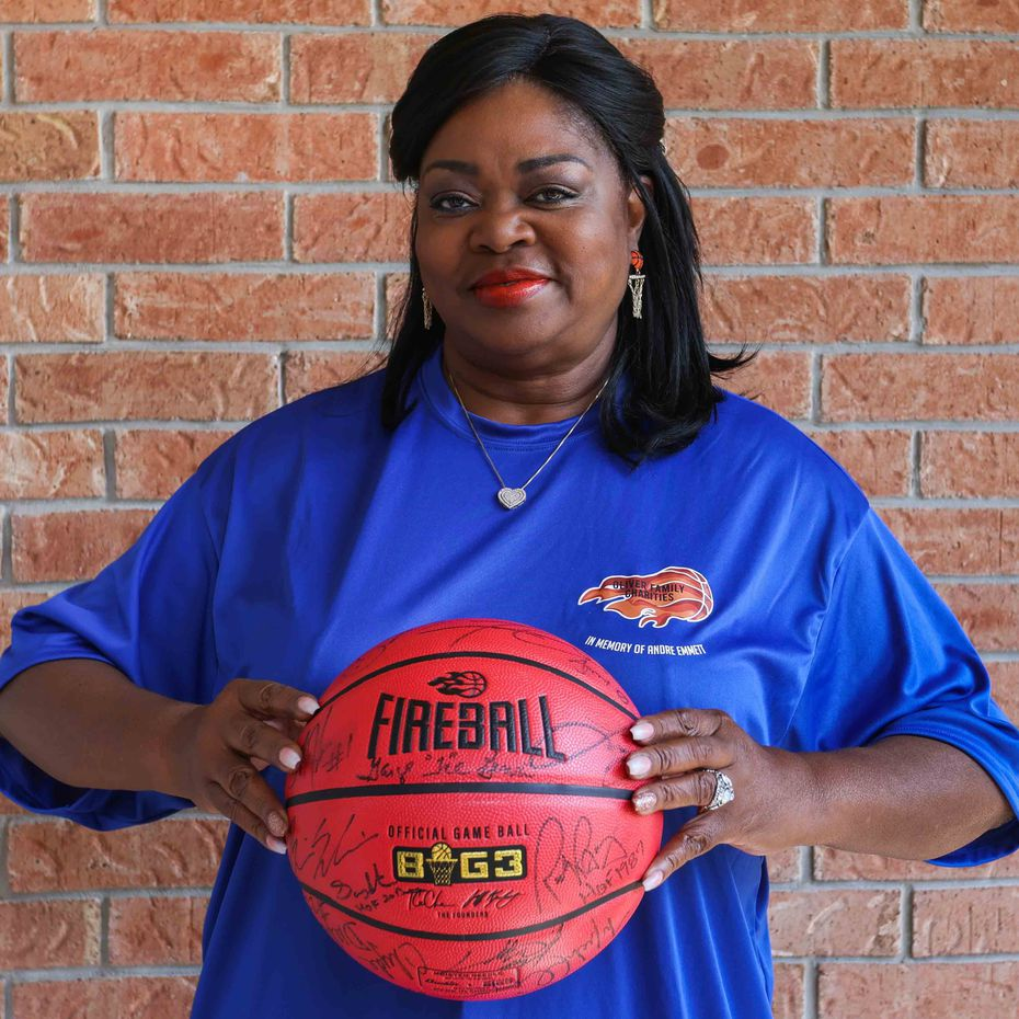 Regina Oliver, mother of Andre Emmett, former Carter HS and Texas Tech basketball star, holds a signed basketball by players and owner of the Big3 league as she poses for a portrait at her home in Cedar Hill on Thursday, August 26, 2021. Emmett was murdered in a robbery two years ago while in town visiting his mother. (Lola Gomez/The Dallas Morning News)