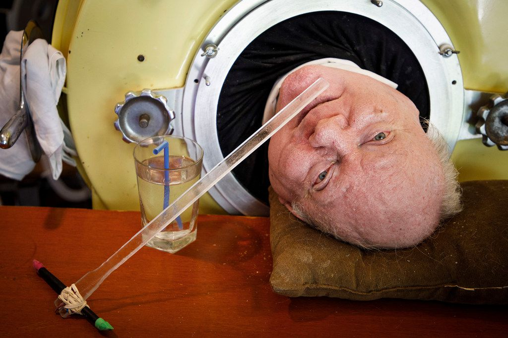 Paul Alexander looks out from inside his iron lung at his home in Dallas.  Now in his 70s, Alexander is one of the few people left who uses an iron lung to help facilitate breathing for those affected by polio.
