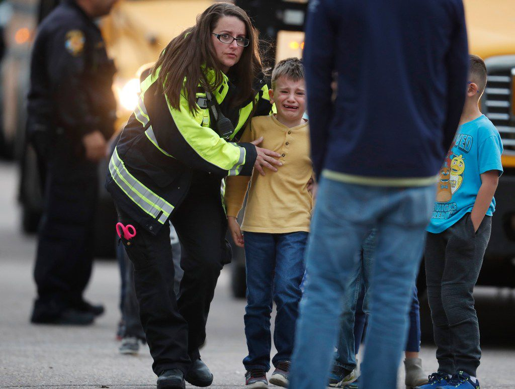 Officials guided students off a bus and into a recreation center where they were reunited with their parents after a shooting at a suburban Denver middle school  in Highlands Ranch, Colo.