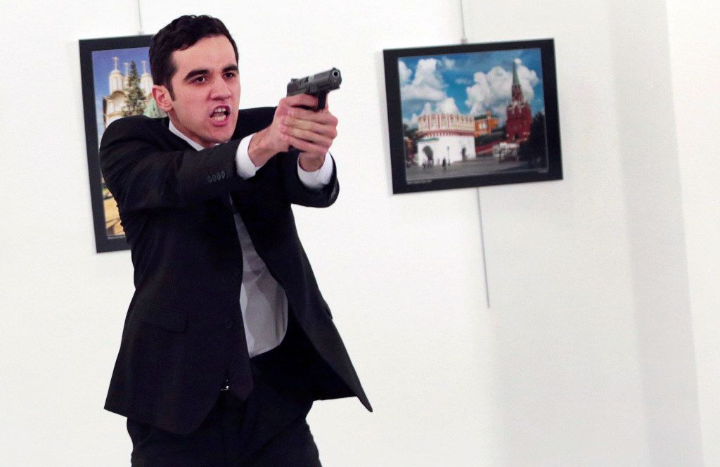 An unnamed gunman gestures after shooting the Russian Ambassador to Turkey, Andrei Karlov, at a photo gallery in Ankara, Turkey, Monday, Dec. 19, 2016. (AP Photo)