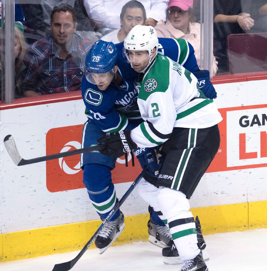 Dallas Stars defenseman Dan Hamhuis (2) fights for control of the puck with Vancouver Canucks center Brandon Sutter (20) during third period NHL hockey action in Vancouver, British Columbia, Sunday, Nov. 13, 2016. (Jonathan Hayward/The Canadian Press via AP)