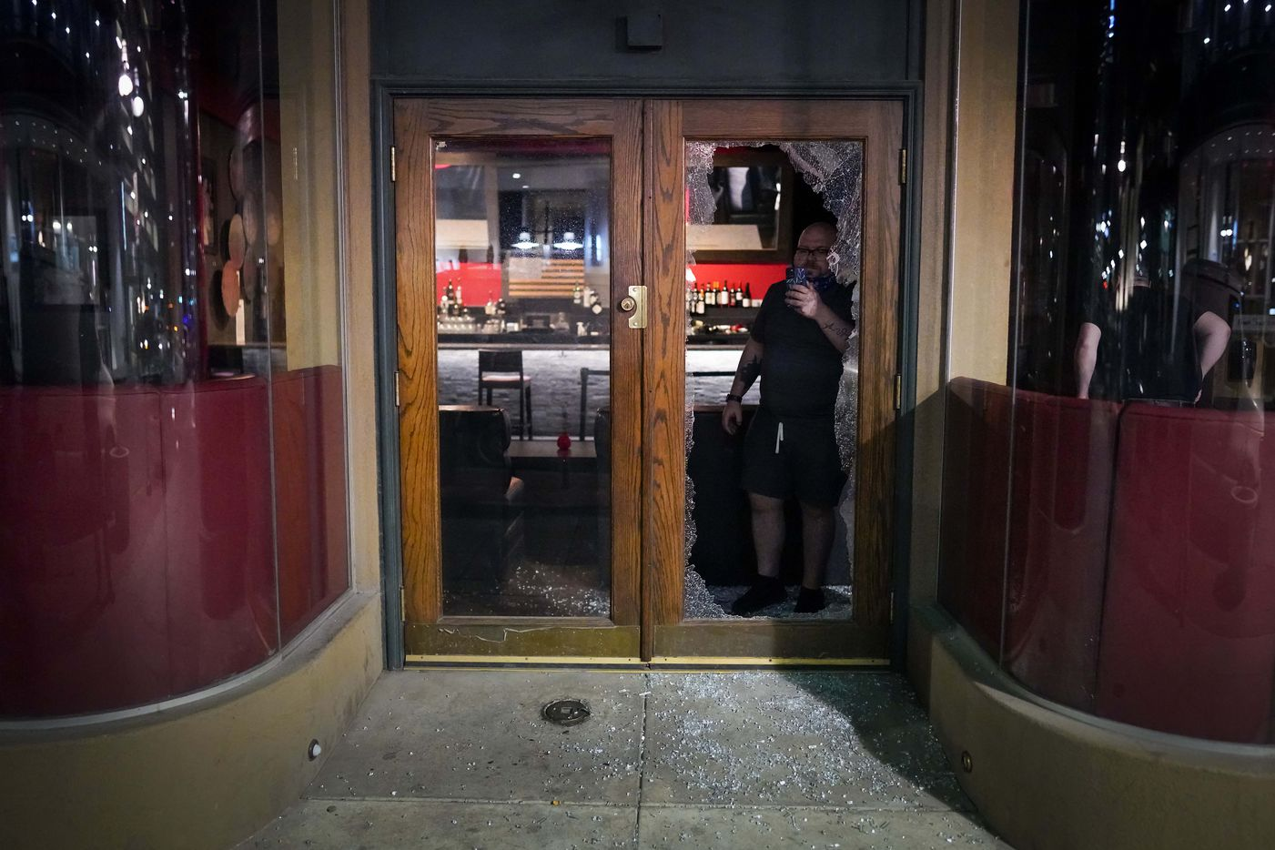 A man takes a photo through the broken glass doorway of Campisi's Restaurant downtown following a protest against police brutality in the early morning hours of Saturday, May 30, 2020, in Dallas.
