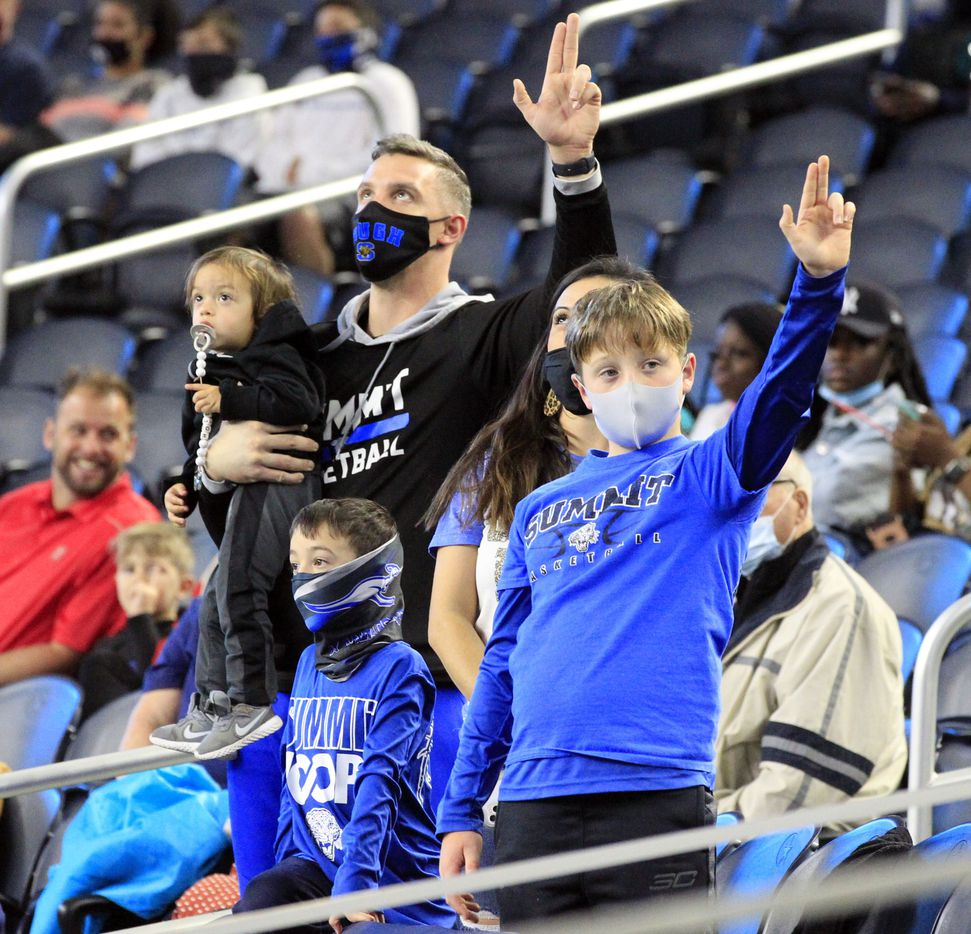A family of Mansfield Summit fans hold their hands high during the school's song before the first half of the Class 5A Division I state semifinal football playoff game against  Denton Ryan at AT&T Stadium in Arlington on Friday, January 8, 2021. (John F. Rhodes / Special Contributor)