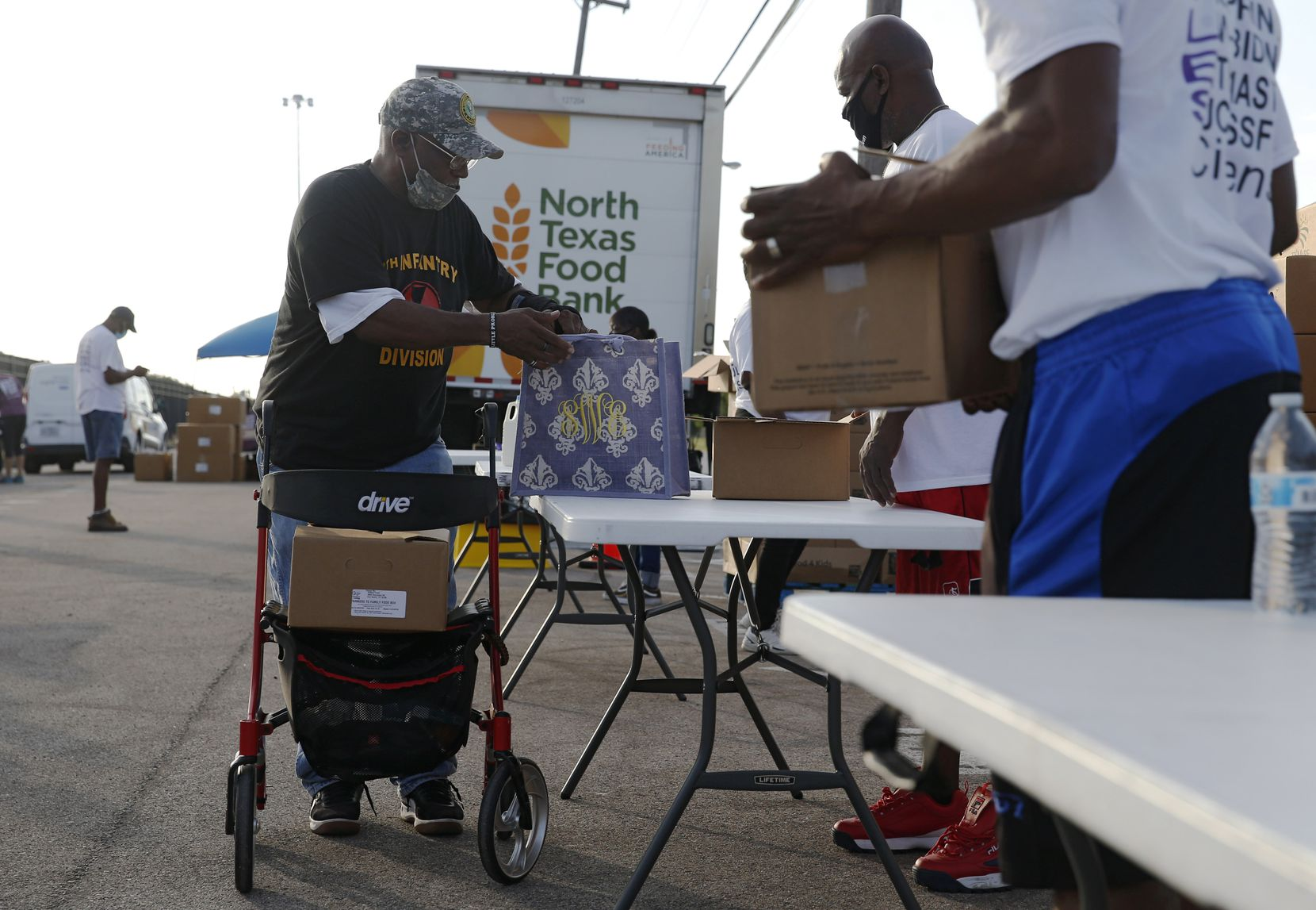Volunteer Alfred Thomas (right) helps Michael Dotson with food as he makes his way through the walk-up line at the North Texas Food Bank's fourth free food distribution at Fair Park.