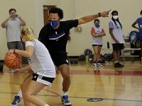 15-year-old Charlotte Collins, left, goes head to head with Jalen Brunson as he interacts with young basketball players during the Mavs Academy Hoop Camp at the Frisco Athletic Center in Frisco, TX, on Jul. 27, 2021.