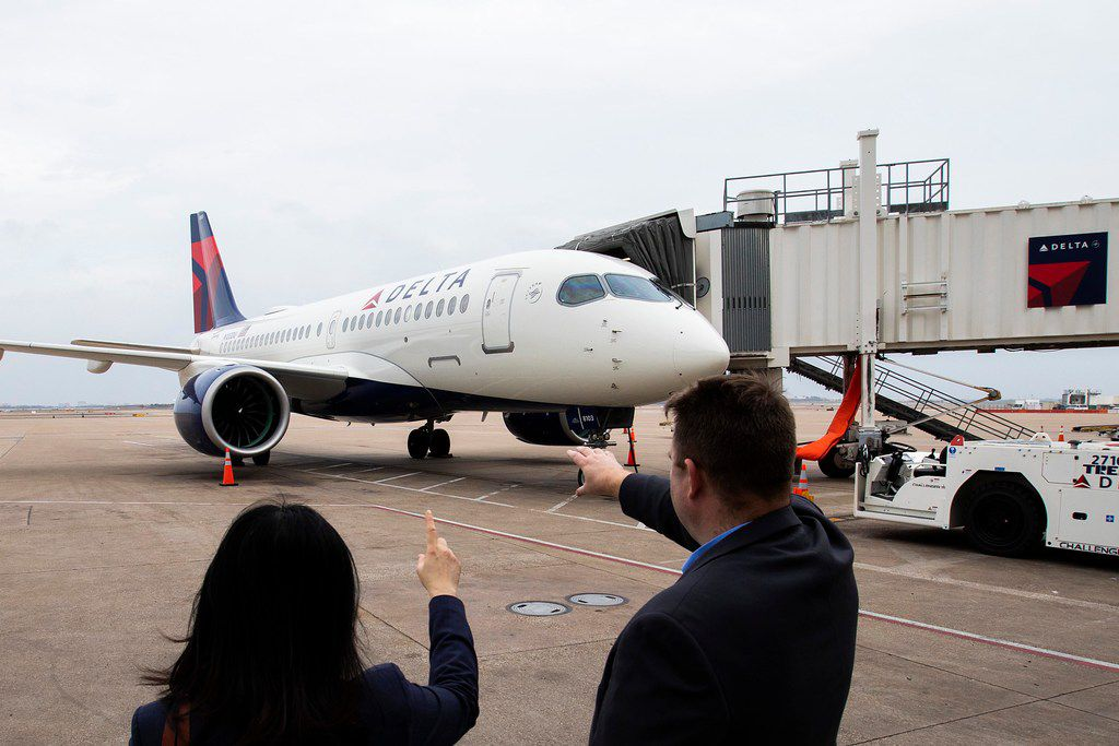 Delta's Airbus A220 airplane sits parked at gate E15 of Terminal E at DFW Airport.