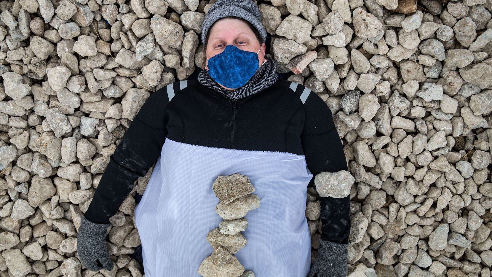 "Erica Felicella lays in a bed of stones as she performs ""Resistance, Re-Live and Proceed"" in the Cedars neighborhood. The piece took place from sunrise to sunset at an empty lot."