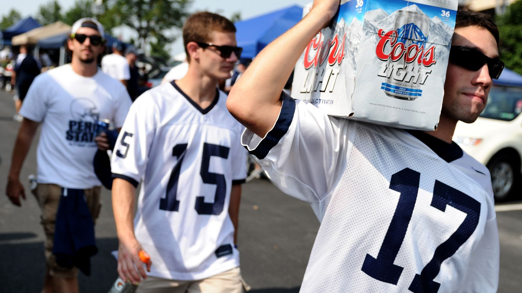 STATE COLLEGE, PA - SEPTEMBER 01: Penn State tailgaters walks with beer in the parking lot prior to the Penn State Nittany Lions playing the Ohio Bobcats at Beaver Stadium on September 1, 2012 in State College, Pennsylvania.