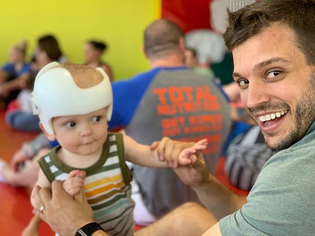 Ryan Layman, with young son Rory, and his husband chose surrogacy in their family planning and ended up influencing a change in how Layman's employer, PwC, provides benefits like surrogacy reimbursement. Newborn Rory wears a helmet to reshape a flat spot on his head.
