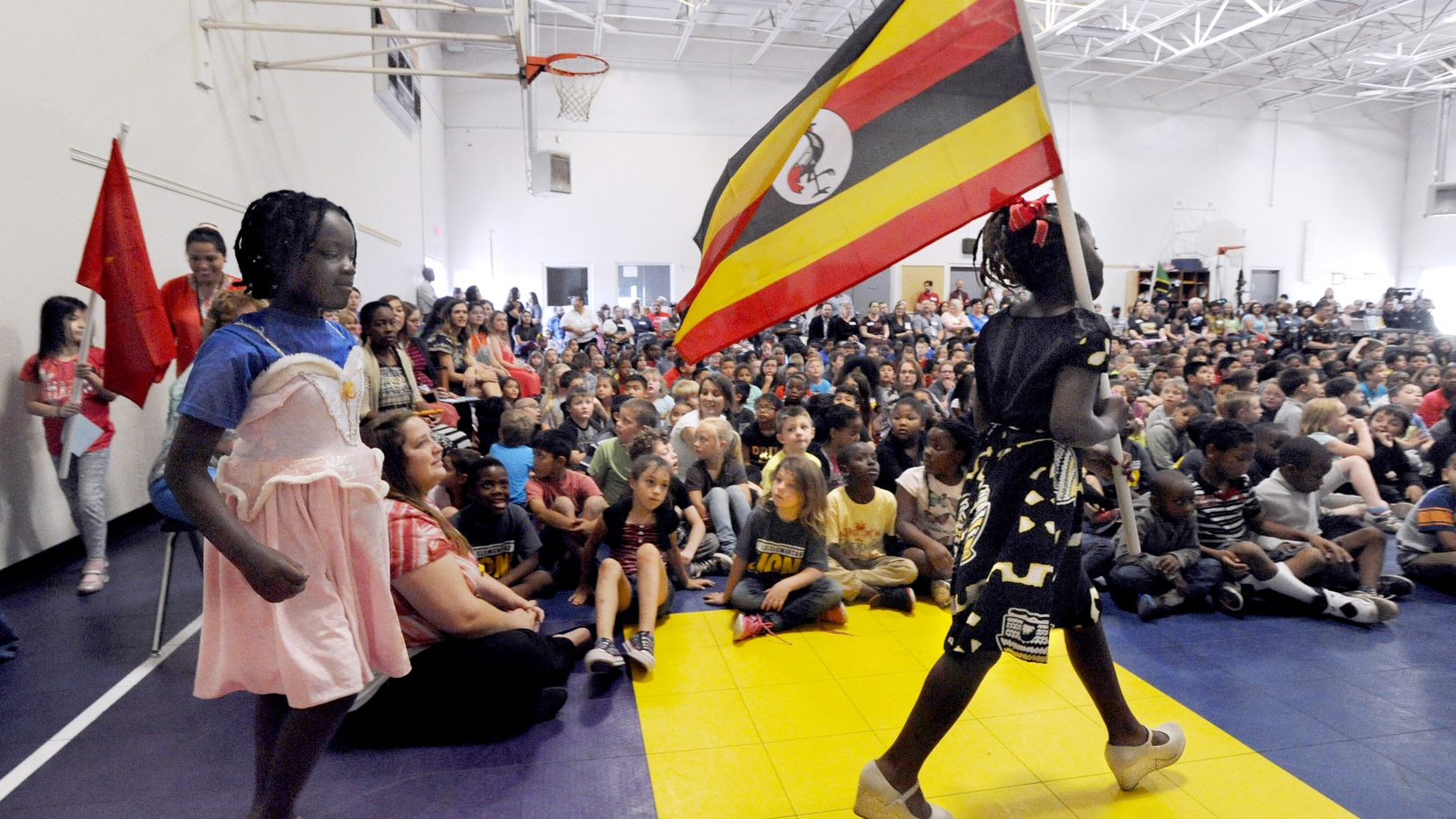 Third-grader Winner Moligi carries the flag of Uganda during a special assembly celebrating the international diversity at Lee Elementary School in Abilene, Texas., Thursday, May 18, 2017. Students from 19 countries carried the flags of the nations from which their families came during the event. The school is the designated entry-point for immigrant families in the Abilene Independent School District. (Ronald W. Erdrich/The Abilene Reporter-News via AP)