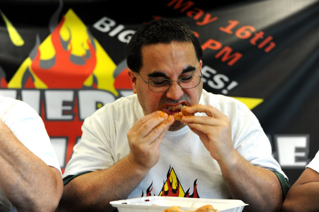 Jason Pick eats wings by Wing Town at the Taste of Irving Fiery Heat Challenge in Irving, TX on May 16, 2015.
