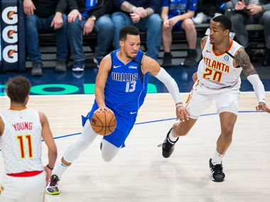 FILE - Mavericks guard Jalen Brunson (13) drives the ball by Hawks forward John Collins (20) during the third quarter of a game on Saturday, Feb. 1, 2020, at American Airlines Center in Dallas.