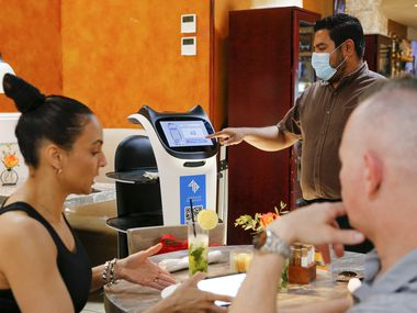 A server sends Panchita, a robot, back to the kitchen after she delivered food to customers at La Duni in Dallas. La Duni has three robots now — and co-owner Taco Borga plans to invest in more.